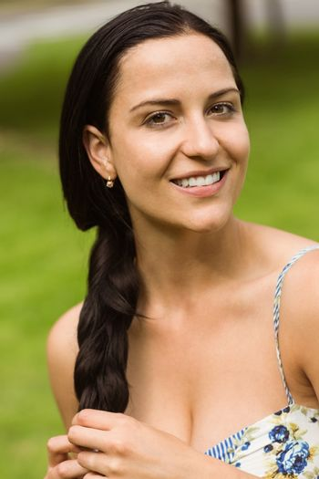 Portrait of a pretty brunette holding her braid