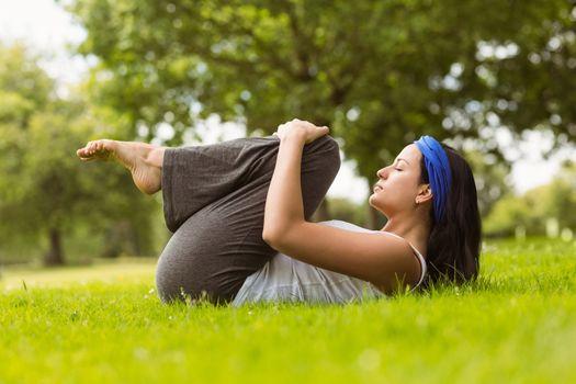 Content brunette doing yoga on grass