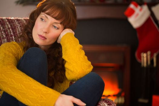 Pretty redhead in day dreaming at christmas