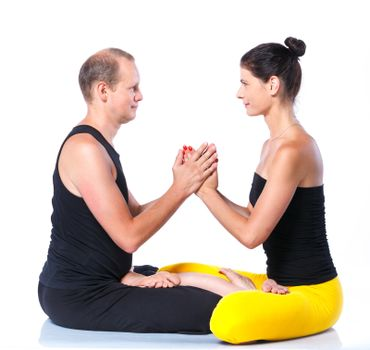 Young couple doing yoga. Isolated on white backgraund