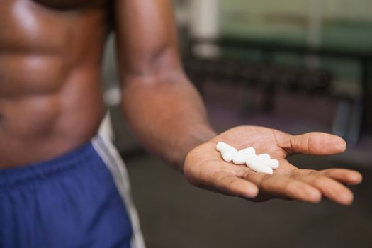Muscular man holding vitamin pills in hand