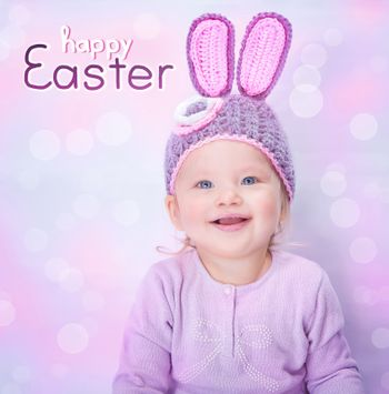 Portrait of cute cheerful Easter bunny, little baby girl wearing pink rabbit ears isolated on blur background, happy spring holiday concept