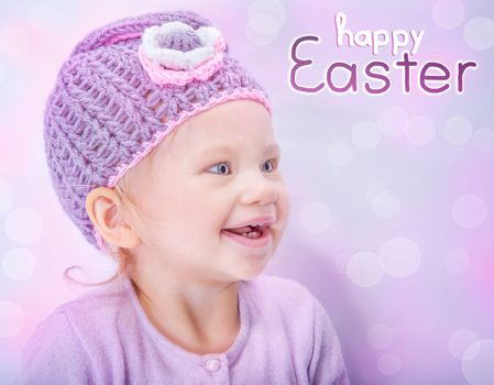 Portrait of happy adorable child wearing cute knitted hat on pink blur background, greeting card with text space, happy Easter holiday