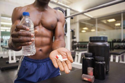 Shirtless muscular man holding vitamin pills