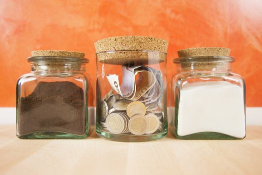 Euro coins and banknotes into crystal jar closed with cork plugs between coffee and white sugar on orange background