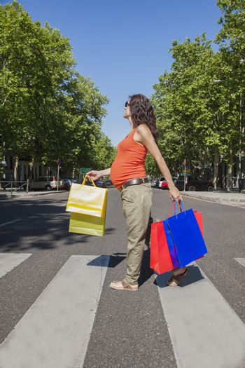 pregnant at crosswalk with shopping bags