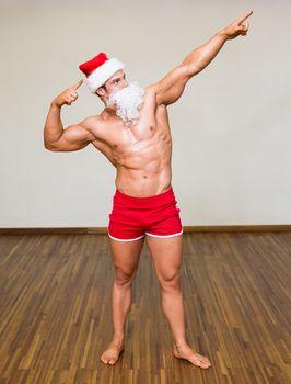 Full length of a body builder in santa costume