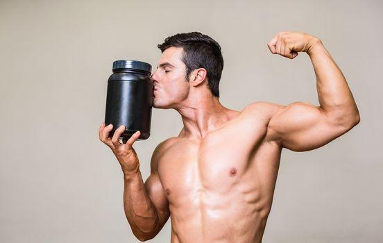 Muscular man kissing nutritional supplement