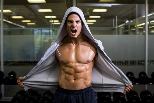 Muscular man shouting in health club