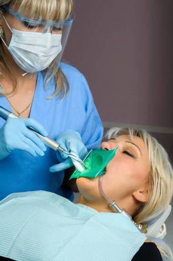 dentist at work with patient, using of dental curing light