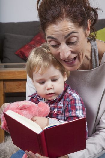 eighteen month aged blonde baby with brunette woman mother reading tale story red book indoor
