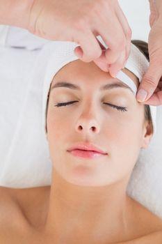 Hand waxing beautiful woman's eyebrow