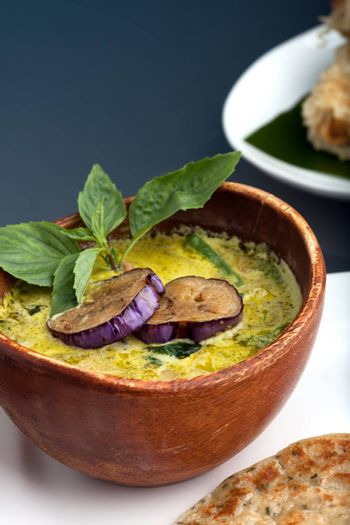 A dish of fresh Thai green curry soup with pancakes and appetizer.
