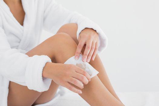 Woman waxing leg at spa center
