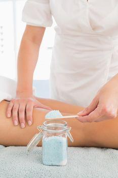 Beauty therapist using salt scrub