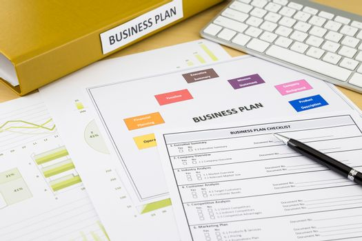 Business plan checklist and documents place on workspace