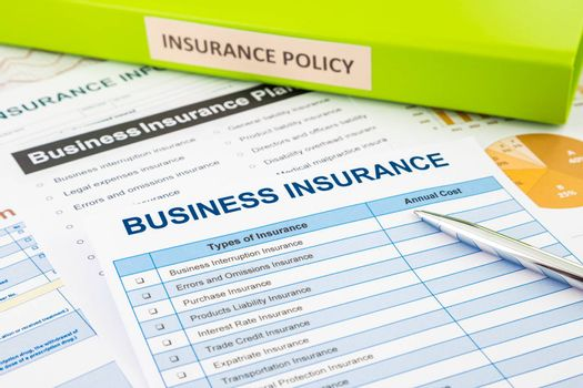 Business insurance planning with checklist forms and document binder, concept for risk management