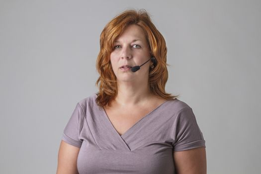 forty years old woman with red hair with headset with an empty look