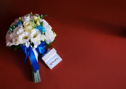 Wedding rings with a bridal bouquet of white roses
