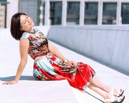 Model in dress posing on exterior set enjoying sun