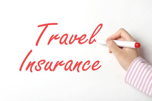 Business woman writing travel insurance word on whiteboard