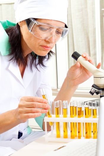 female scientist microscoping in the life science research laboratory (genetics, biochemistry, forensics, microbiology)