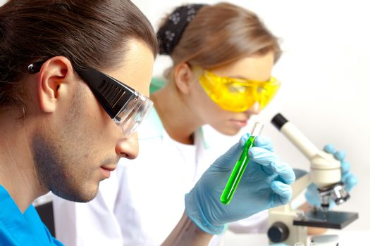Male researcher analyzes tubes and his colleague looking through the microscope