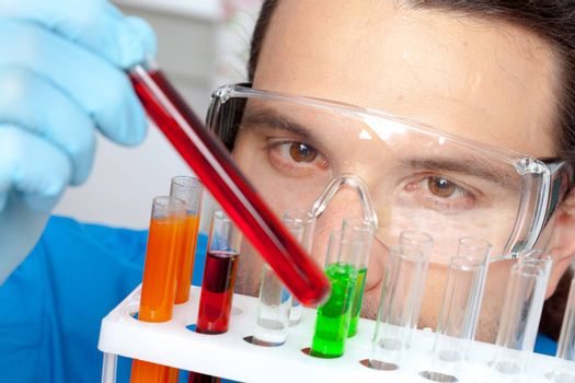Lab worker examining contents of a test tube