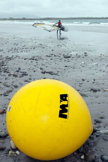 giant  Irish windsurfing association yellow buoy on a beach in the wild atlantic way