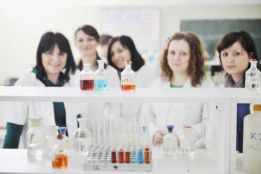 young woman students group in bright chemistry  lab