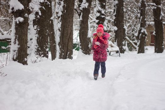 Little girl in winter pink hat in snow.
