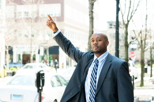An African American business man raises his hand to hail a cab in the city.