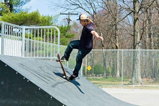 Action shot of a skateboarder on a skateboarding ramp at the skate park.