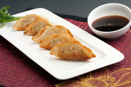 Fried thai gyoza dumpling appetizers with soy dipping sauce.