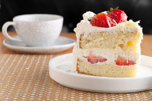 Slice of strawberry shortcake with white chocolate shavings.