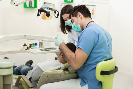 Surgery At The Dentist Office - Doctor Is Working On The Patients Mouth With The Help Of An Assistant