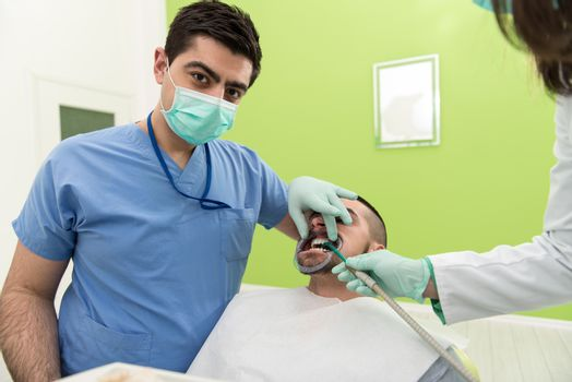 Male Patient With Dentist And Assistant In A Dental Treatment - Wearing Masks And Gloves