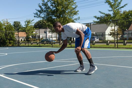 A sweaty young basketball player dribbling down the court demonstrating his ball handling skills.
