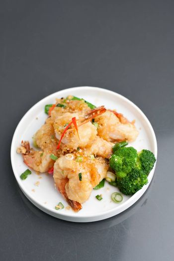 Thai style honey shrimp dish presented beautifully on a round white plate with copy space above.