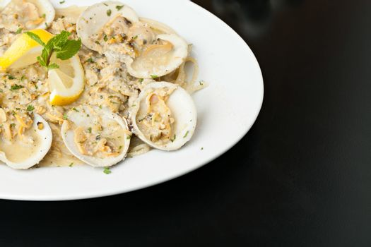 Italian pasta dish with fresh clams over pasta with copy space.