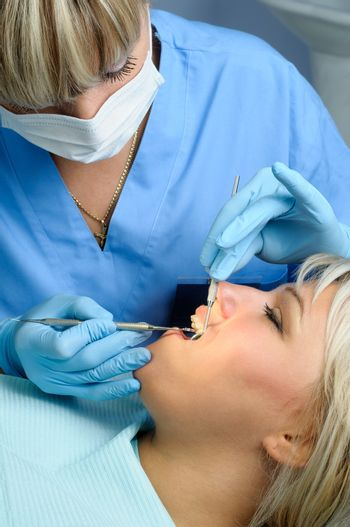 dentist at work with patient, dental exam, polishing and finishing