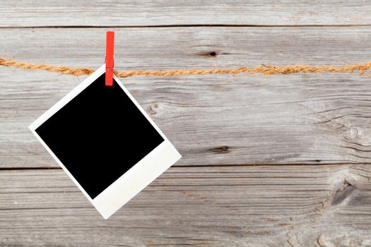Blank photo hanging on a clothesline over wooden background