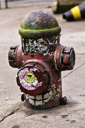 Old and dirty red hydrant on the sidewalk