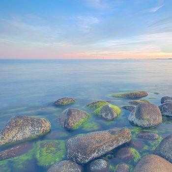Sunset over the rolling stones of the Norwegian coast, Moelen