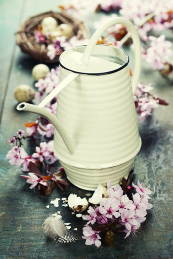 Easter composition with little watering can and Cherry Blossom branches