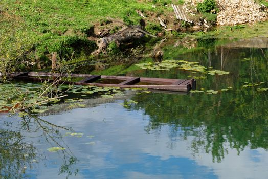 Sunken old wooden boat in summer river