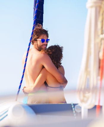 Back side of happy loving young couple standing on the deck of sail boat, spending honeymoon in sea cruise, happiness and love concept