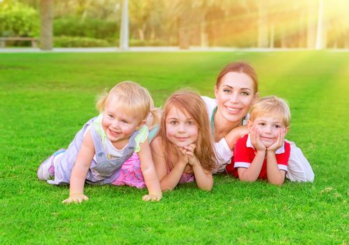 Happy family having fun outdoors, beautiful mother with three cute little children lying down on fresh green grass, enjoying spring season