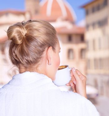 Back side on woman having morning coffee in the hotel, wearing white robe and enjoying cityscape from the window, Europe, Italy, Florence