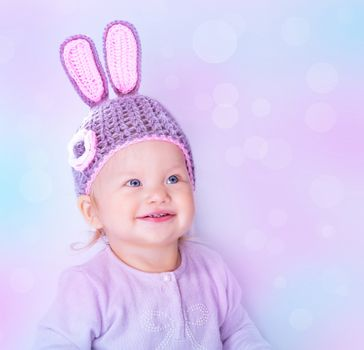 Portrait of happy cute baby girl wearing knitted hat with rabbit ears on purple blur background, beautiful Easter bunny